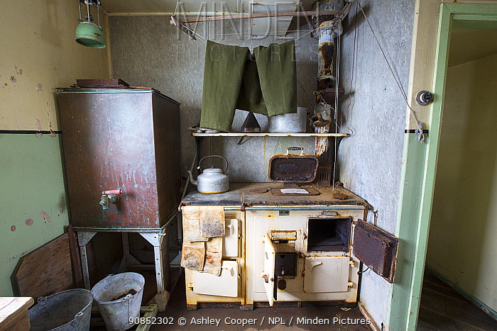 Trousers drying above kitchen stove, as left when researchers were evacuated in 1959. Station W, former British scientific research station, Detaille Island, Graham Land, Antarctica. 2020.