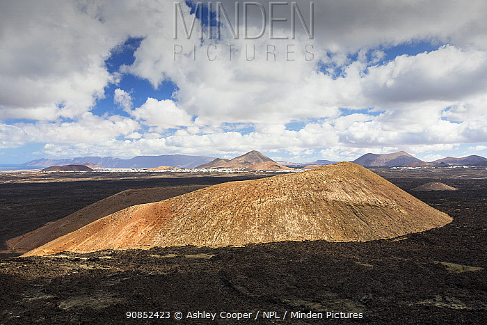 Montana Caldereta, a volcano formed by eruptions in the 18th Century, surrounded by volcanic rock. View from Caldera Blanca, Lanzarote, Canary Islands, Spain. November 2019.