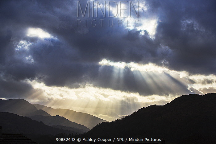 Sun rays shining through clouds onto Loughrigg Fell and hills of the Lake District National Park, in evening. Ambleside, Cumbria, England, UK. April 2020.