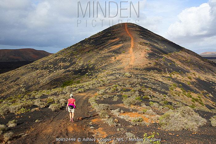 Woman walking on path up Montana Los Rodeos, Lanzarote, Canary Islands, Spain. November 2019.