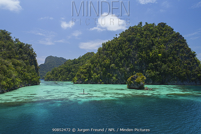 Tourist paddle boarding in lagoon between karst islands covered in rainforest, aerial view. Raja Ampat Islands, West Papua, Indonesia. 2018.