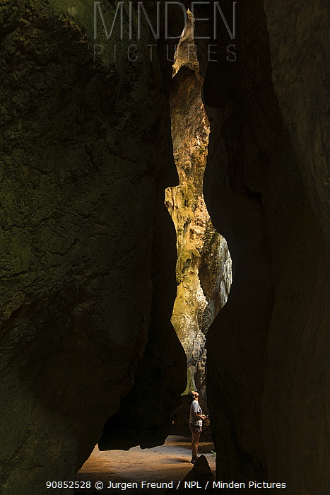 Woman standing in chasm within limestone cave. Chillagoe-Mungana Caves National Park, North Queensland, Australia. 2015.