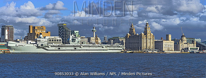 HMS Prince of Wales aircraft carrier moored at the Liverpool Pierhead on the River Mersey with the Three Graces building on the right, Liverpool, England, UK, March 2020.