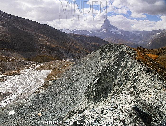 Lateral moraine deposited at edge of Findel glacier. Glacier in retreat with braided river in valley, Matterhorn in distance. Zermatt, Valais, Switzerland. September 2019.