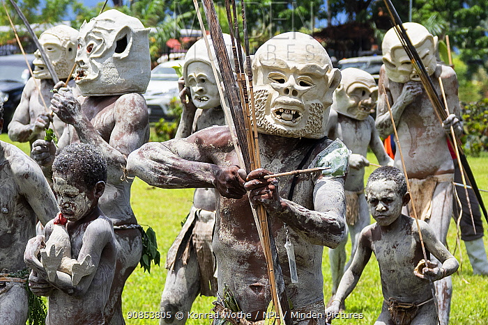 Mudmen, Papuan men in traditional clay masks, bodies painted with clay, boys also painted. At Sing-sing gathering where traditional cultures including dance and music are shared. Morobe Show, Lae, Papua New Guinea. 2019.