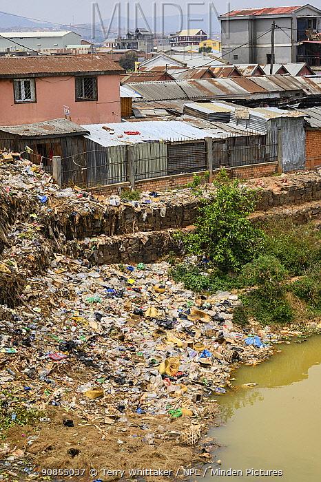Plastic rubbish on bank of River Ikopa, houses in background. Mandroseza, Antananarivo, Madagascar. 2019.
