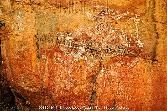 Aboriginal rock art depicting group of people and Namarrgon the lightning spirit. Lightning storms in October and November signal the beginning of the wet season. Nourlangie, Kakadu National Park, Northern Territory, Australia.