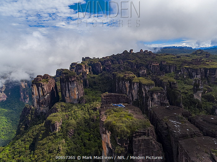 People alongside helicopter with film camera mounted, on tepui table-top mountain, aerial view. Taken on location for BBC Seven Worlds One Planet series. Canaima National Park, Venezuela. 2018.