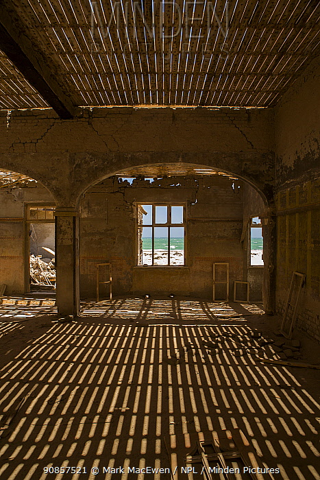 Abandoned building at former diamond mine, shadows of roof panels cast on sand covered floor, desert reclaiming the mine. Elizaeth Bay, Namibia. 2017.