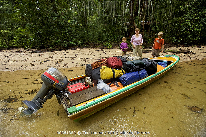 Orangutan researcher Cheryl Knott, with children Russell and Jessica, with loaded boat, ready to depart from Cabang Panti Research Station, Gunung Palung National Park, Borneo. August 2010 Model released.