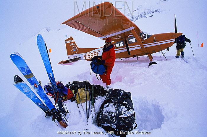 Skier Phil Atkinson unloads mountaineering gear from a ski plane on the Ruth Glacier, Denali National Park, Alaska, USA