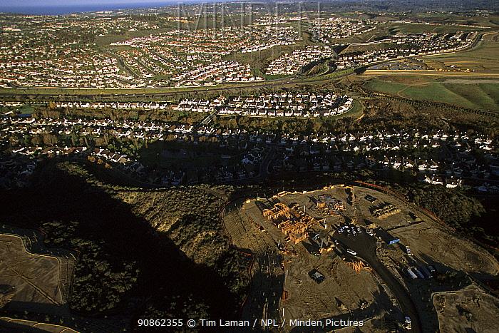 Aerial view of freeway and housing construction in coastal sage scrub habitat, North San Diego County, California. Dec 2002.