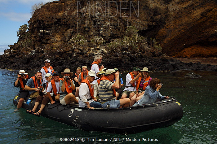 Group of tourists in inflatable boat beside the shore of Punta Cormorant, Floreana (Charles) Island, Galapagos Islands, Ecuador, Nov 2007.