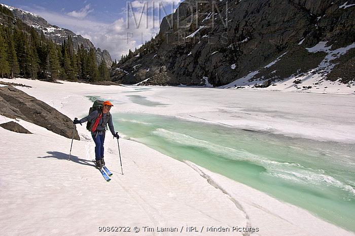 Skier Phil Atkinson skiing past Rimrock Lake, Beartooth Mountains, Montana, USA May 2008
