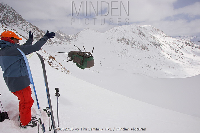 Skier Phil Atkinson tosses his pack from an 11,500 ft pass near Granite Peak, Beartooth Mountains, Montana, USA. May 2008