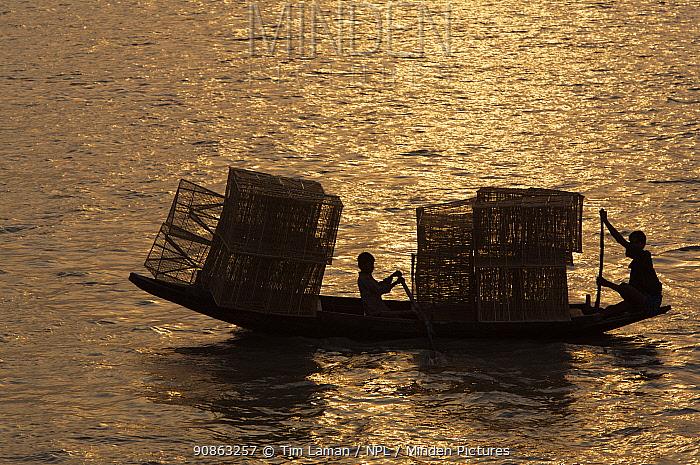 Boys transporting fishing traps by boat on the Kholpatura River, Sundarbans, Khulna Province, Bangladesh, March 2006