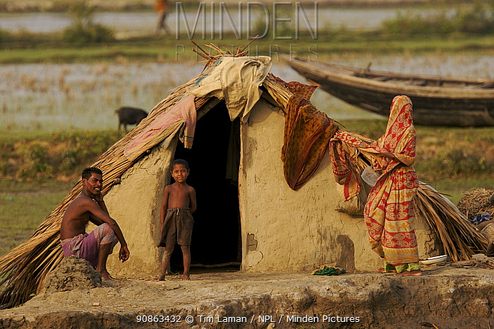 Villagers in the village of Chandpai on the Passur River, where shrimp fry fishing to supply shrimp for the shrimp ponds is the main industry. Villagers live in simple mud and thatch huts that are washed away by high waters every year. Sunderbans, Khulna Province, Bangladesh, April 2006