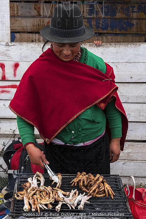 Woman tending chicken feet barbecue, Calpi animal market, Parish of Riobamba, Chimborazo Province, Andes, Ecuador. July 2016.