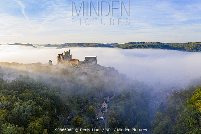 Beynac Castle in the mist, Beynac-et-Cazenac Village, Dordogne, France, October 2020.