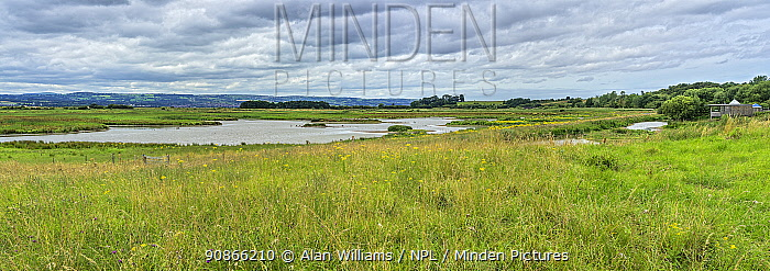 RSPB Burton Mere wetlands showing the scrape and the visitor centre on the right ,with the hills of North Wales in distance, UK. July 2020