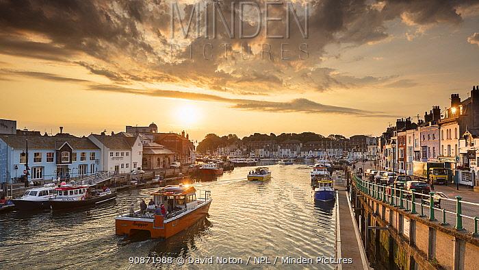 Fishing boats leaving Weymouth Harbour at sunrise, Jurassic Coast, Dorset, England, UK. August 2019.