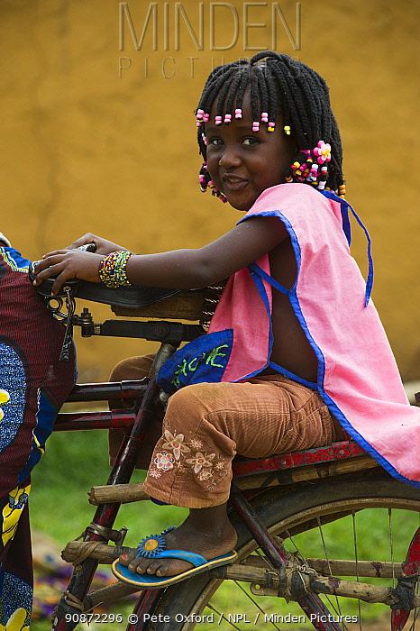 Young girl on back of bicycle, Mbomo Village, Odzala-Kokoua National Park, Republic of Congo (Congo-Brazzaville), Africa, May 2013.