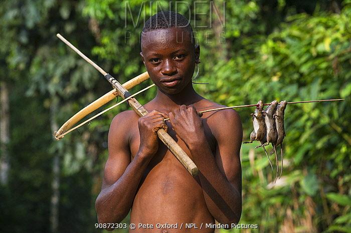 Boy with homemade crossbow used to shoot rats. Mbomo, Odzala-Kokoua National Park, Republic of Congo (Congo-Brazzaville), Africa, June 2013.