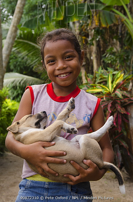 Local girl holding sleeping puppy, Kioa Island, Fiji, South Pacific, July 2014.
