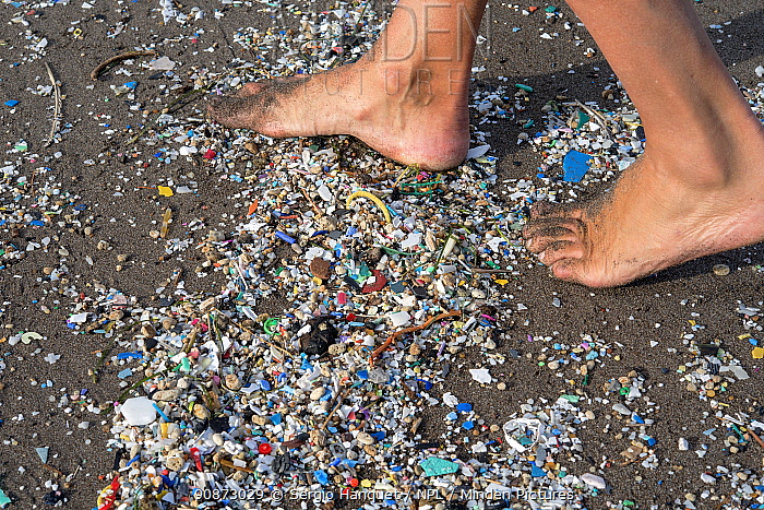 Person walking over plastic and microplastics covering the beach, brought in by the winds and the tides, Canary Islands.