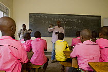 African Golden Cat (Profelis aurata) researcher, Sam Isoke, giving lecture in primary school, part of an educational activity to teach children about forest animals, western Uganda  -  Sebastian Kennerknecht