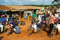 Men with motorbikes and mopeds, outside shops in shanty town slums, Kampala, Uganda  -  Wayne Hutchinson/ FLPA
