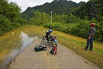 Man with motorbike looking at road impasssable after flooding, Phong Nha Ke Bang National Park, Vietnam  -  Matthew Maran/ npl