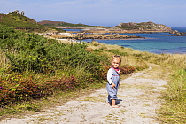 Girl, aged 16 months, standing on path to Little Bay, St. Martin's, looking back, Isles of Scilly. August. Model-released.