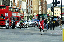 Cyclist and motor cyclist pulling away from traffic light during the rush hour, Angel, London Borough of Islington, England, UK, May 2009
