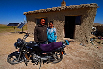 Mongolian shepherd Ge Ri Li Ao De and his wife Ao Te Gen with their motorbike in front of house with solar panels, Inner Mongolia, China. May 2016
