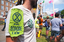 Extinction Rebellion protester wearing logo and 'Make Ecocide Law' message. Climate change rally, Bristol, England, UK. 16 July 2019.
