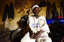 Voodoo healer / azeto of Djenan Temple, motorbike and mural of lion in background. Abomey, Benin, 2020.