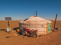 Nomadic Ger / yurt camp with modern motorbike and solar panel. Gobi Desert. Mongolia.