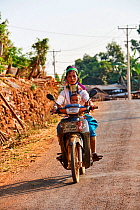 Kayan Lahwi woman with brass neck coils and traditional clothing riding a motorbike with her child. The Long Neck Kayan (also called Padaung in Burmese) are a sub-group of the Karen ethnic people from...