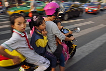 Woman and three children on a scooter/motorbike, Xia Shan area in the Zhan Jiang city, Guangdong, China, November 2015.