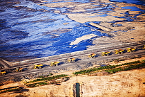 Massive dump trucks queuing to load with tar sand in front of a toxic wasteland. Syncrude mine, Athabasca, Alberta, Canada, 2012